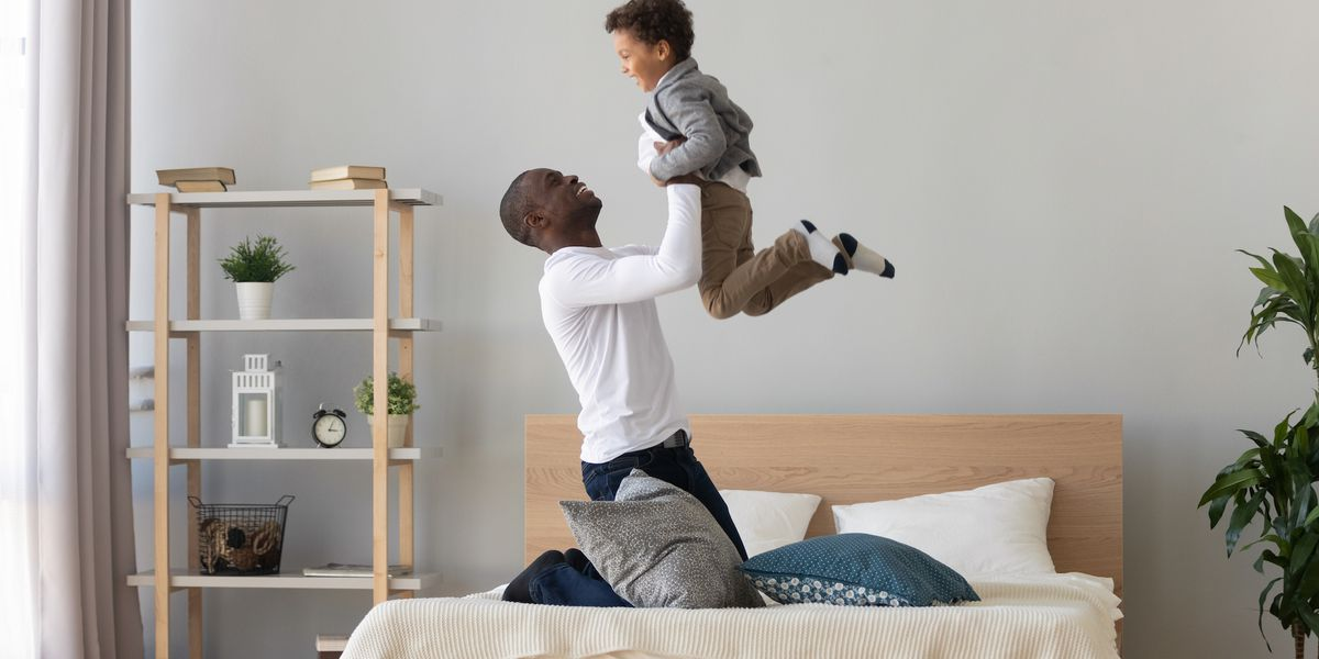 Happy family loving black father holding lifting cute small mixed race child son playing on bed, funny little kid boy flying in single african american dad arms having fun feel joy bonding in bedroom